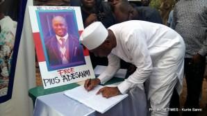 Senate President, Bukola Saraki signing the condolence register at Late Pius Adesanmi candlelight tribute