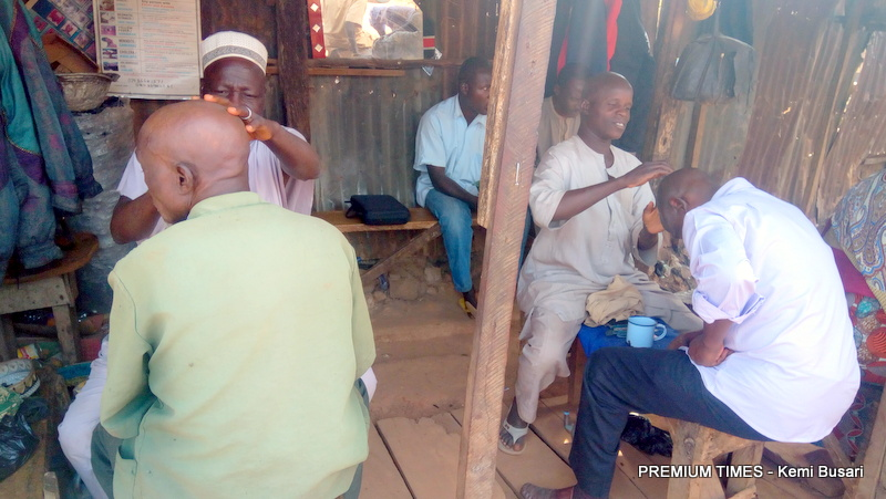 Kaduna local barbers shaving their customers