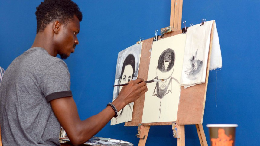 One of the exhibiting visual artists captured while painting his canvas