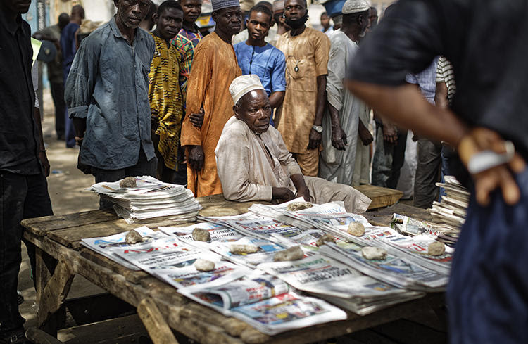 People gather around a newspaper stand in Kano, northern Nigeria, on February 24, 2019. Journalist Obinna Don Norman was recently charged under Nigeria's 2015 cybercrime act. (Ben Curtis/AP)