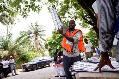 A man raises a ballot paper during the counting of governorship and state assembly election results in Lagos, Nigeria, on March 9, 2019. (Adelaja Temilade/Reuters)