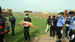 Dead five year old carried by poliemen.
