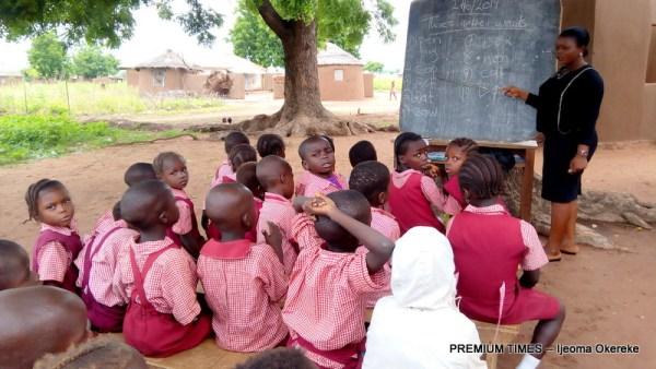 Nursery Three pupils learning under tree
