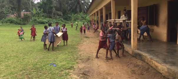 Pupils carrying the new desks into classrooms (1)