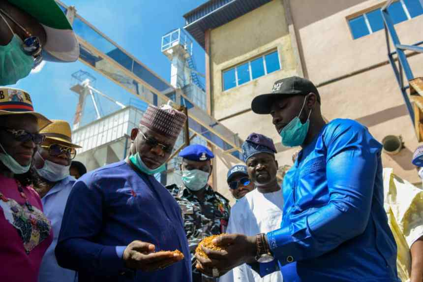 Governor Yahaya Bello inspecting grains at the completed factory