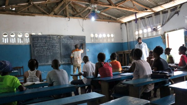 Koroma stands watching as a volunteer teacher teaches school children at the Alagendra Secondary School, preparing them to write the West Africa Senior Secondary Certificate Examination