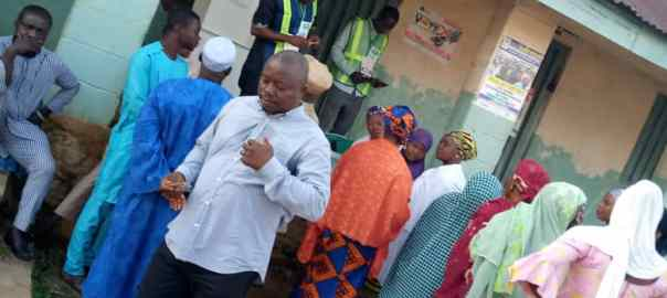 7:19am PU002, Ward 002, LGEA School Ogominana, Adavi LG, Kogi. Electorates are queuing up for their accreditation while some are checking for their names on the Voters registration list pasted on a wall nearby. INEC officials are seen arranging the cubicle, ballot boxes and other sensitive materials.