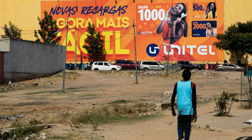 An Angolan walks by the a shopping mall with a Unitel advertisement in Angola.