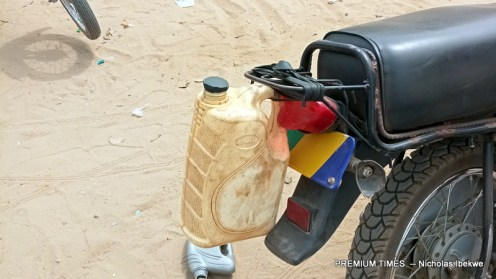 An Okada rider with 5-litre keg tied to his motorcycle