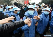 Chinese health workers and volunteers pictured wearing face masks and protective jackets to stay safe from Coronavirus (Covid-19)