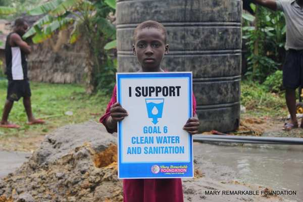 A boy in Edonwick, Eastern Obolo, holds a placcard to endorse UN declaration on water and sanitation