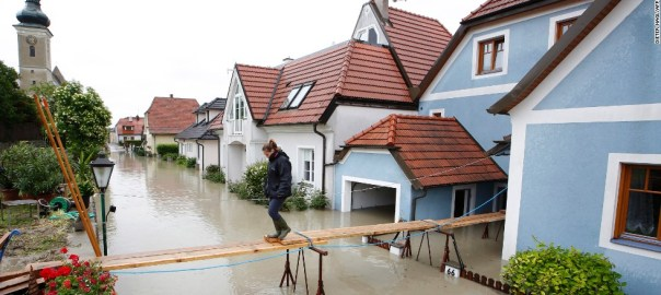 A woman crosses a makeshift bridge over streets in Unterloiben, Austria on June 4, 2013. Torrential rain and heavy flooding hit central Europe. AFP PHOTO / DIETER NAGL