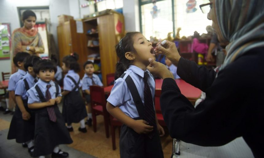 A Pakistani health worker administers polio vaccine drops to a child at a school during a polio vaccination campaign in Karachi on April 9, 2018.