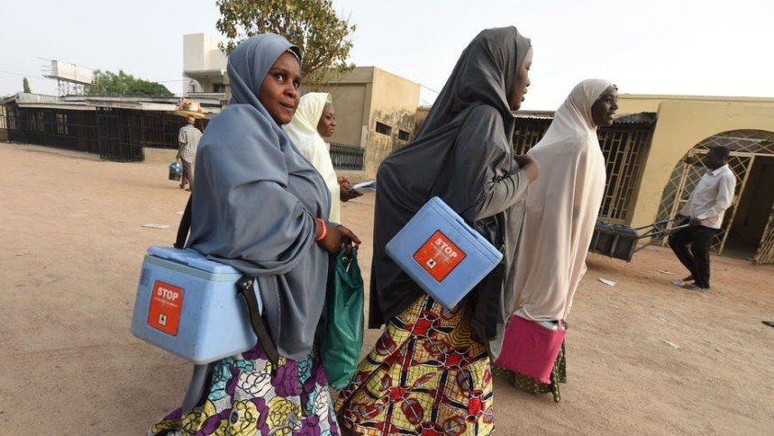Health workers walk from house to house during vaccination campaign against polio in Kano, northwest Nigeria in 2017. Photo by Pius Utomi Ekpei/AFP via Getty Images. [PHOTO CREDIT: The Conversation]