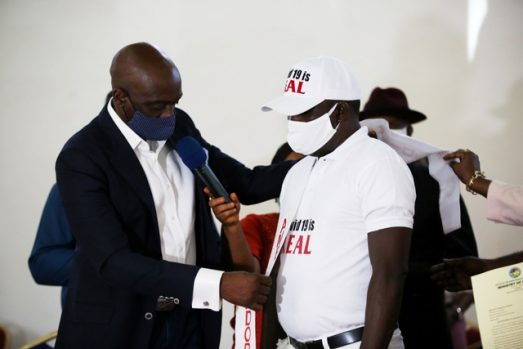 Secretary to Delta State Government, Mr. Chiedu Ebie Esq. (left) Decorating Chief Austin Eruotor, as Delta State Ambassador for the fight against COVID-19, held in Government House, Asaba. PIX: BRIPIN ENARUSAI