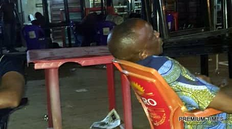 Picture of a Vigilante official demanding protection level from passengers stranded at the Old Tollgate in Asaba