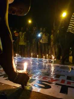 Protester holds a Nigeria flag as people hold a vigil for those who have died during the protest whole others light candles to honour the dead