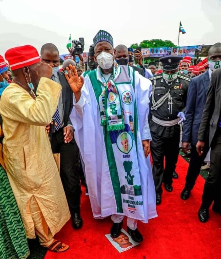 Ganduje stepping on Kwankwaso's picture celebrating democracy day