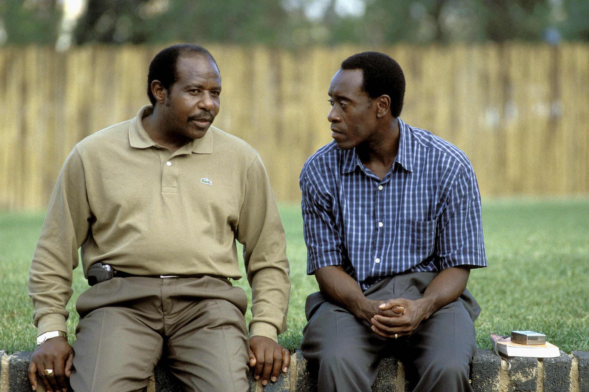 Paul Rusesabagina and Don Cheadle on the set of Hotel Rwanda. [PHOTO CREDIT: AF Archive/Alamy Stock Photo]