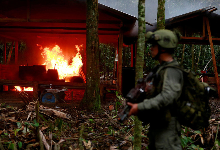 An anti-narcotics policeman stands guard after burning a cocaine lab in a rural area of Guaviare state, Colombia, on August 2, 2016. [Credit: REUTERS/John Vizcaino/File Photo]