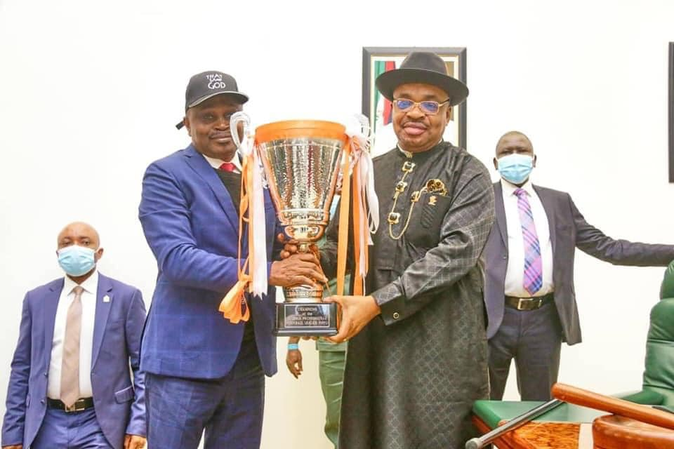 Governor Emmanuel receiving the trophy from the sports commissioner, Mr Monday Uko
