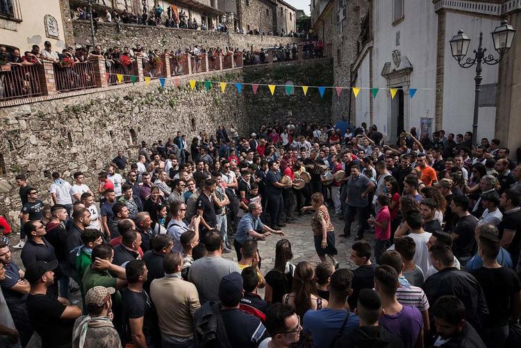 The faithful dancing in the typical Calabrian tradition during the celebrations for Santa Maria di Polsi, in the square in front of the sanctuary. [Credit: Michele Amoruso/Pacific Press/Alamy]