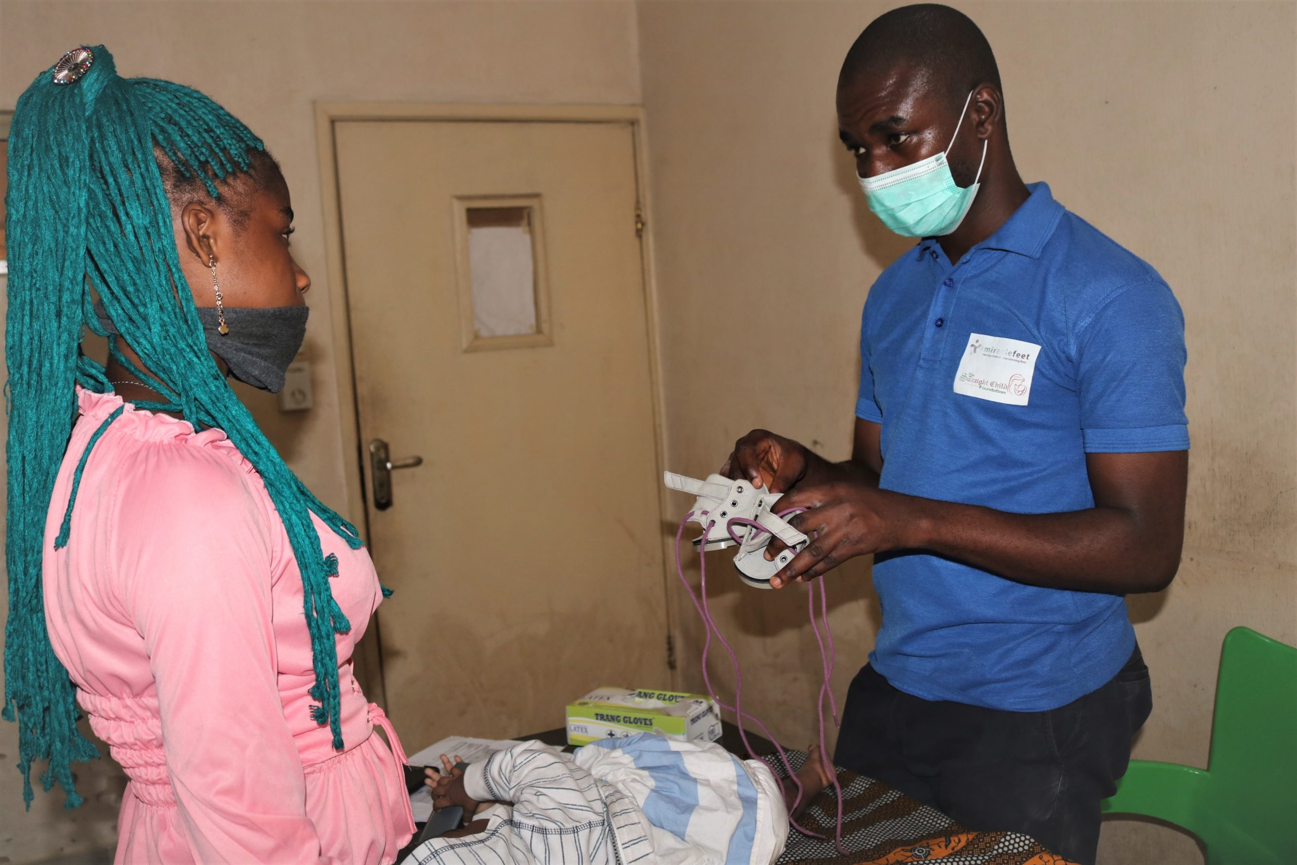 Tochukwu Ekwueme, a clinic asstistant, explains to a mother the function of the shoe and how it is worn.