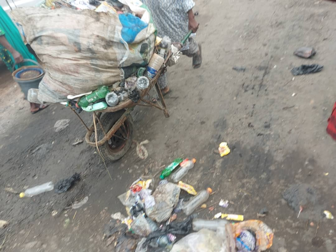 A cart pusher heading to the dumpsite to dispose of waste