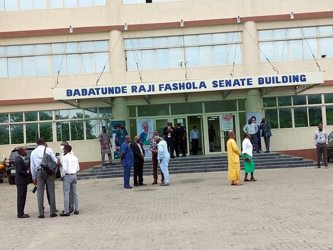 Workers awaiting the new VC at the entrance of the university's senate building