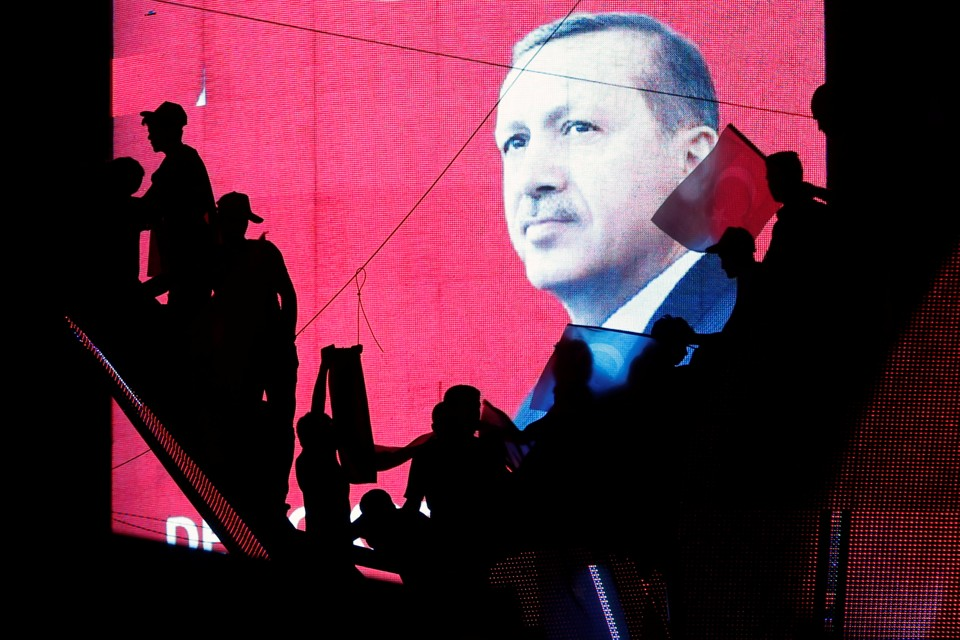 Turkish Supporters are silhouetted against a screan showing President Tayyip Erdogan during a pro-government demonstration in Ankara