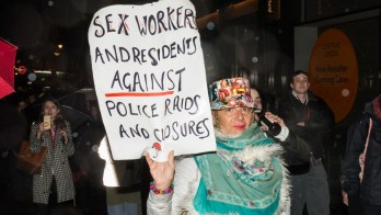 """A woman holds a sign that says """"Sex workers and residents against police raids and closures."""""""