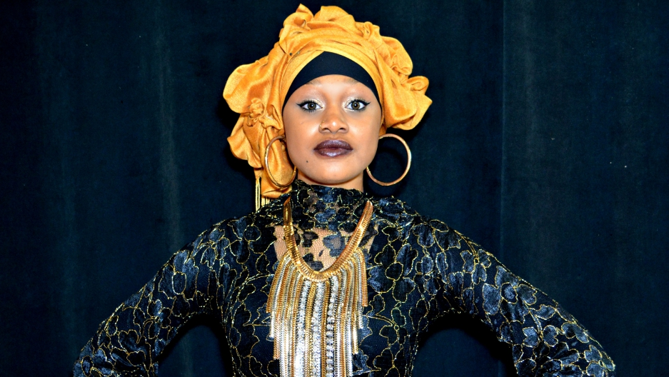 A woman wearing a headwrap and as shimmering blue and gold dress stands in front of a camera, with her hands to her hips.