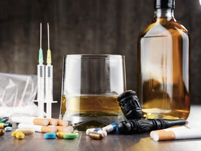 array of drugs and alcohol sitting on table