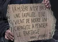 Deux mains tiennent un vieux carton avec les mots : La misère n'est pas une fatalité. Elle vient de notre incapacité à penser le partage. - Abbé Pierre.