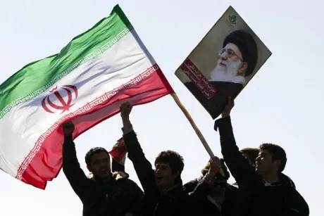 Demonstrators wave Iran's flag and hold up a picture of supreme leader Ayatollah Ali Khamenei during a ceremony to mark the 33rd anniversary of the Islamic Revolution, in Tehran's Azadi square February 11, 2012.