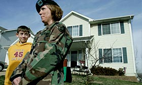 Iowa National Guard Staff Sgt. Lyndsay Thrane, shown with her son, bought a home in Urbandale, Iowa, with help from a homebuying program for veterans. (© Charlie Neibergall/AP)