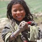 Glad flicka i bergsby. Tibet