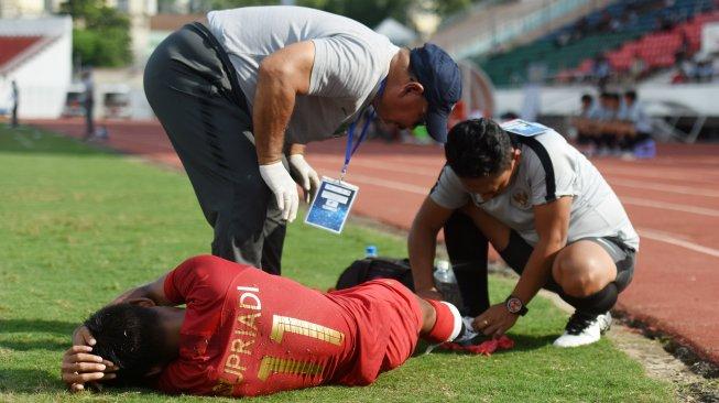 Pemain Timnas Indonesia U-18 Supriadi (bawah) mendapat perawatan dari tim medis saat bertanding melawan Laos pada penyisihan Grup A Piala AFF U-18 2019 di Stadion Thong Nhat, Ho Chi Minh, Vietnam, Senin (12/8/2019). ANTARA FOTO/Yusran Uccang