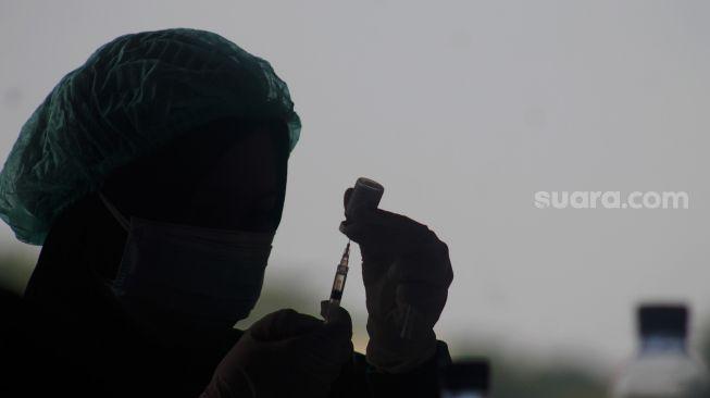 Petugas kesehatan bersiap menyuntikan vaksin di Pelabuhan Sunda Kelapa, Jakarta Utara, Jumat (11/6/2021).  [Suara.com/Dian Latifah]
