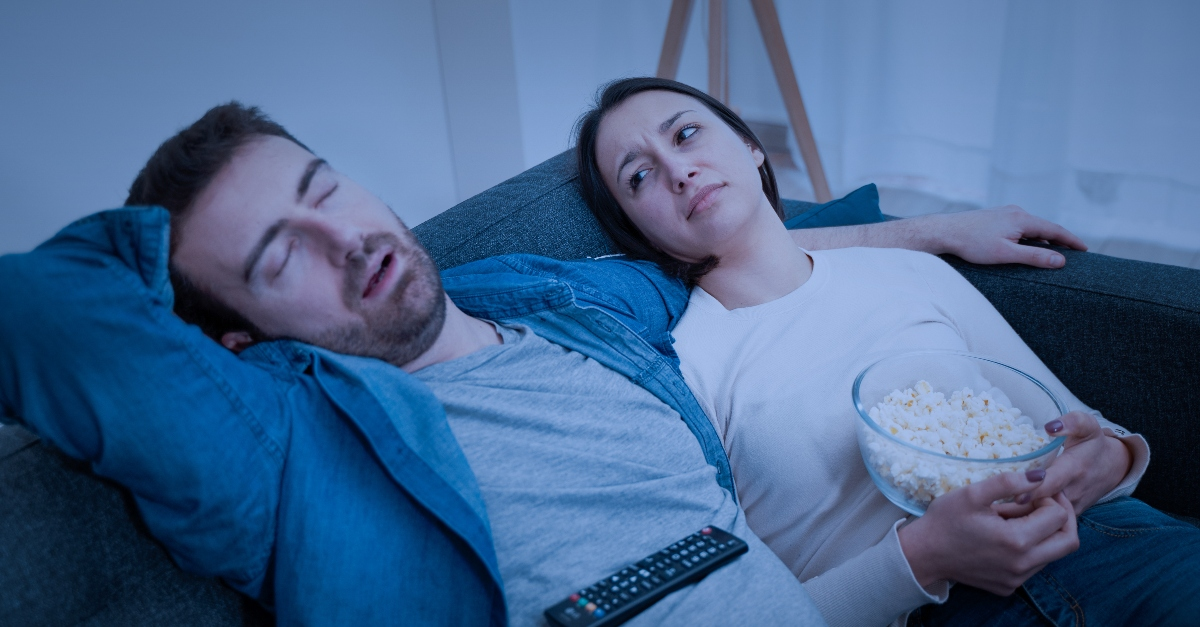 couple sitting on couch with popcorn watching movie looking tired and annoyed, keep marriage alive under lockdown