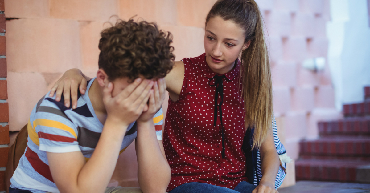 young woman comforting teen boy looking distressed