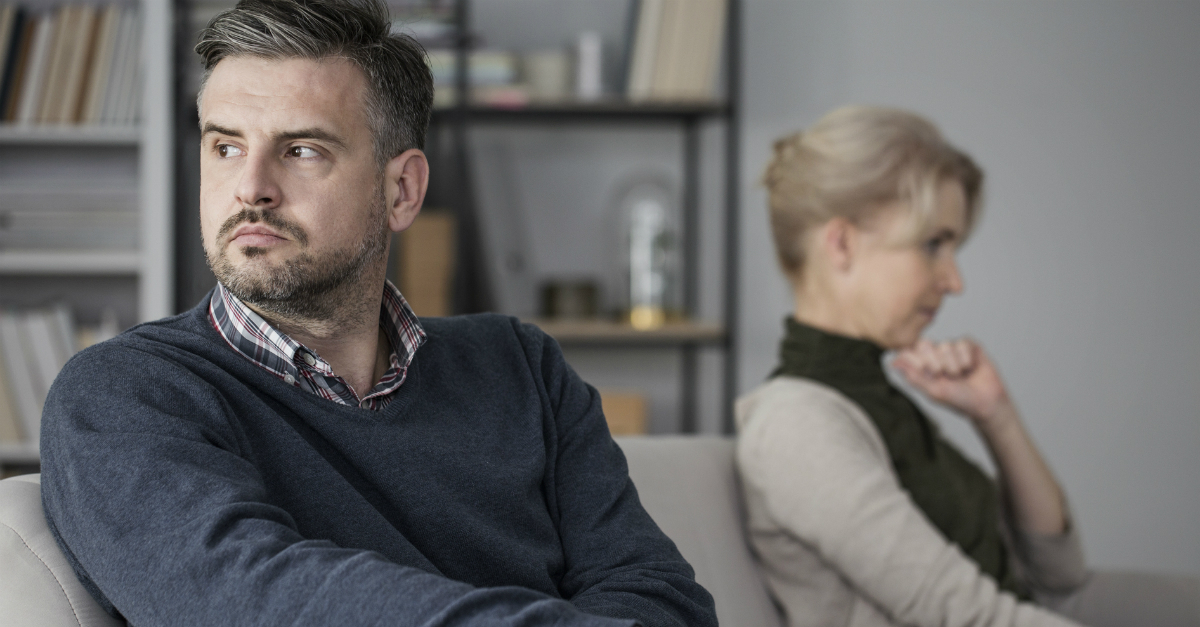 mature couple sitting upset looking away from each other on couch, shame undermines marriage