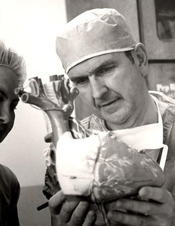 Russell M. Nelson explica un procedimiento quirúrgico a una enfermera.