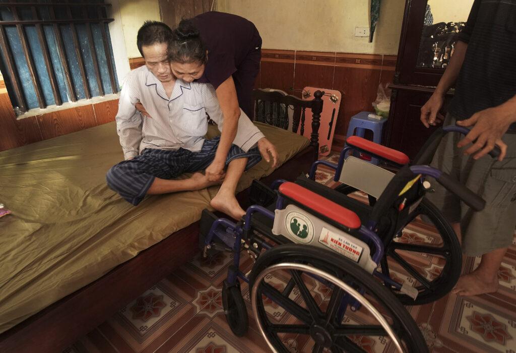 Bao Dinh Tran es ayudado por su esposa Quyen Thi Mai a subir a su silla de ruedas que recibió de Latter-day Saints Charities en Hanói, Vietnam, el sábado, 16 de noviembre de 2019.