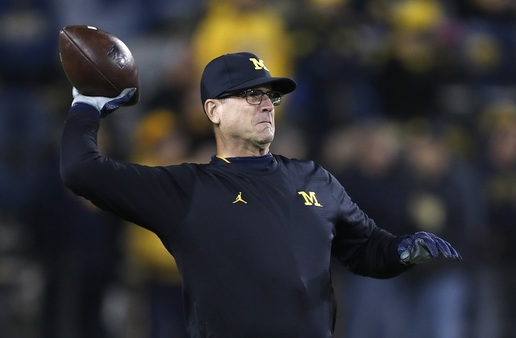 Michigan head coach Jim Harbaugh throws a football on the field before an NCAA college football game against Iowa on Nov. 12, 2016. Thanks to a creative compensation plan that includes cash value life insurance, Harbaugh is college football's top-paid coach. (AP Photo/Charlie Neibergall)