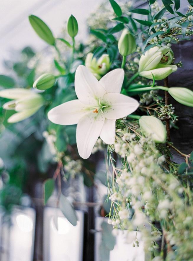 placerkortstavla dekorerad med vita blommor och grönt