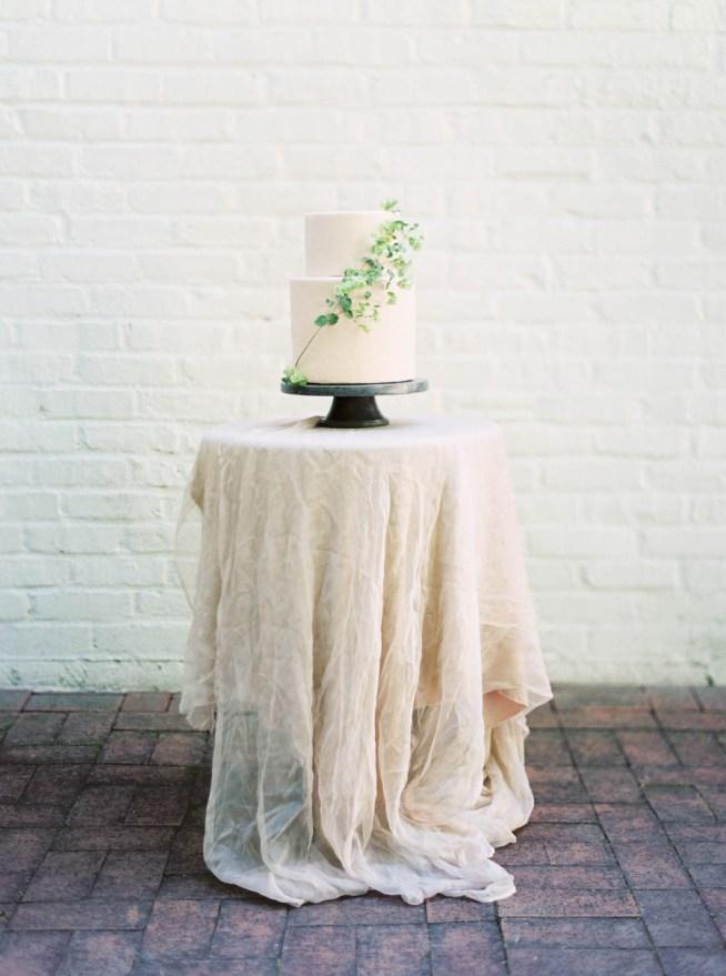 vit bröllopstårta dekorerad med gröna blommor