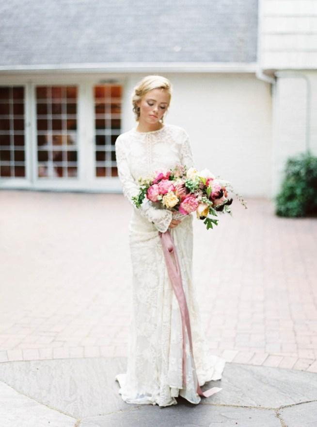 brud i vit spetsklänning med en brudbukett i rosa och gult