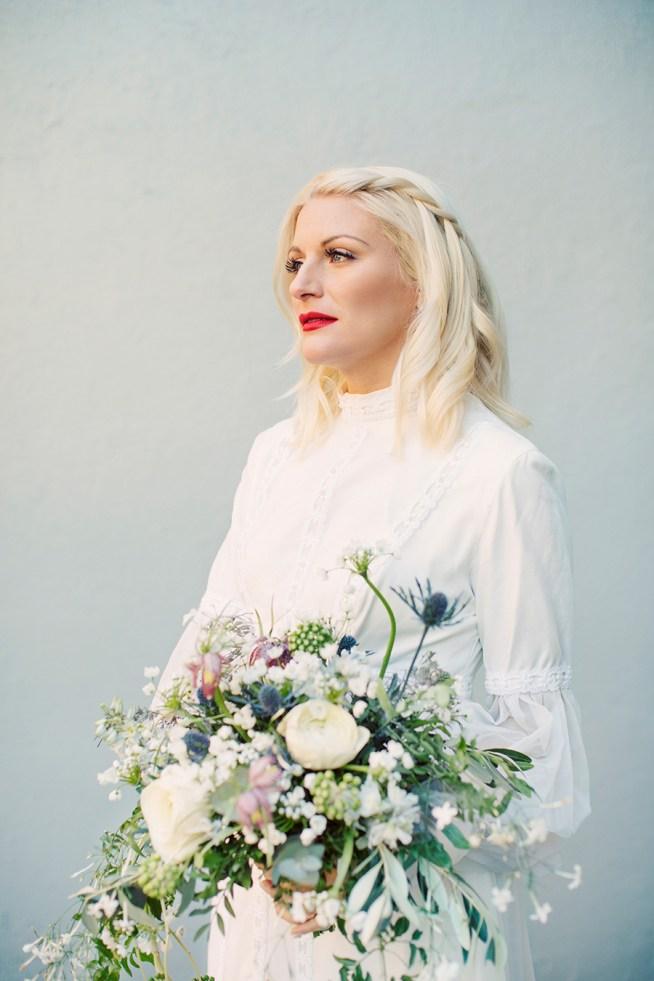 Brud i vintageklänning med en vårin brudbukett med ranunkler