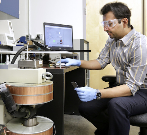 """Oak Ridge National Laboratory's Ayyoud Momen works on the team's """"breadboard"""" prototype refrigerator-freezer: a flexible platform used to evaluate material compatibility and to analyze components including the magnet, generators, motor, pump, heat exchangers, plumbing and leakless rotating valve. ( ORNL.)"""